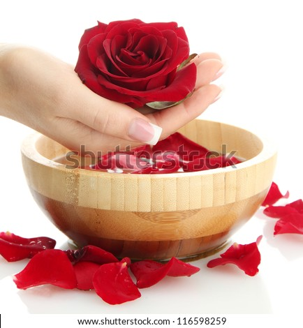 woman hand with wooden bowl of water with petals, isolated on white - stock photo