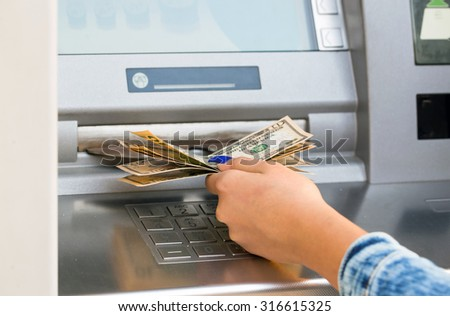 woman hand withdrawing money from outdoor bank ATM - stock photo