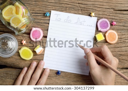 woman hand write to do list on wooden table with jelly candy - stock photo