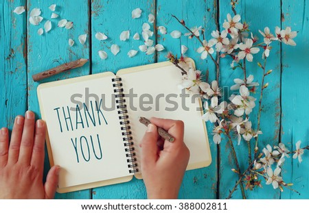 woman hand writing a note with the text thank you on a notebook, over wooden table and cherry blossom flowers - stock photo