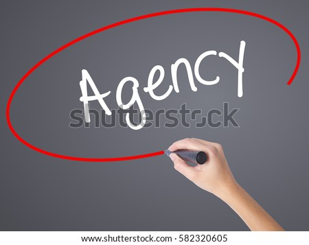 Woman Hand Writing Agency with black marker on visual screen. Isolated on  grey. Business