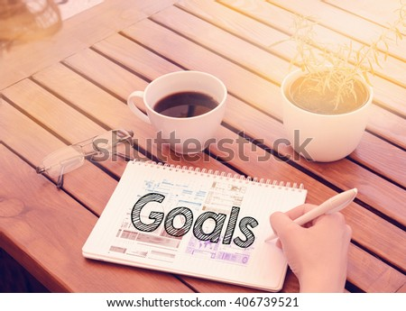 Woman hand writing in notebook on wooden table with coffee, plant and glasses - goals - stock photo