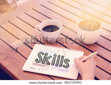 Woman hand writing in notebook on wooden table with coffee, plant and glasses - skills - stock photo