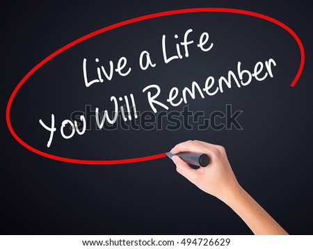 Woman Hand Writing Live a Life You Will Remember on blank transparent board with a marker isolated over black background. Business concept. Stock Photo