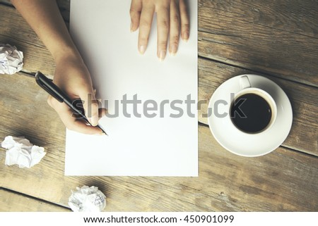woman hand writing with pen on notebook and coffee cup on wood table background