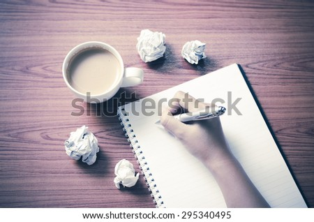 woman hand writing with pen on notebook.there are crumpled paper and coffee cup on wood table background vintage style - stock photo