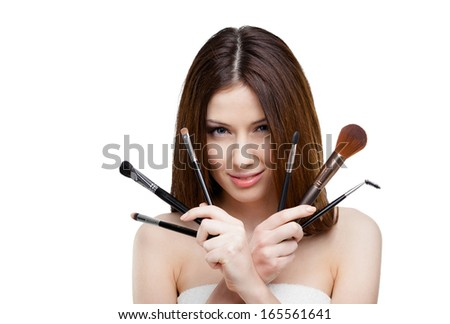 Woman handing a set of cosmetic brushes for makeup, isolated on white - stock photo