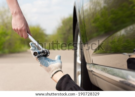 Woman handing a socket wrench or spanner to a mechanic working underneath her car after it has broken down at the side of a rural road - stock photo