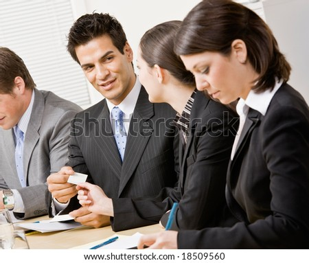 Woman handing co-worker business card in meeting in conference room