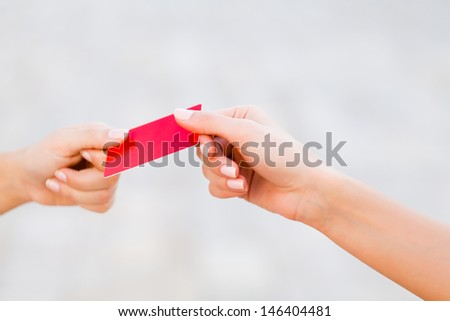 Woman handing credit card to the other woman hand.