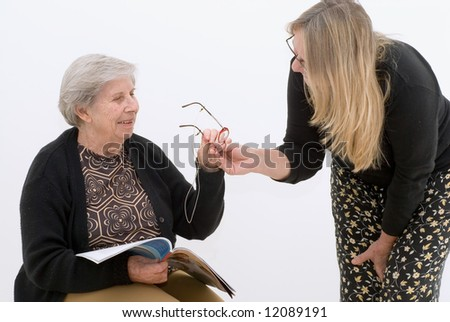 Woman handing reading glasses to her elderly mother. Isolated against a white background