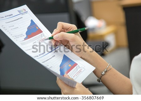 Woman hands checking graph - stock photo