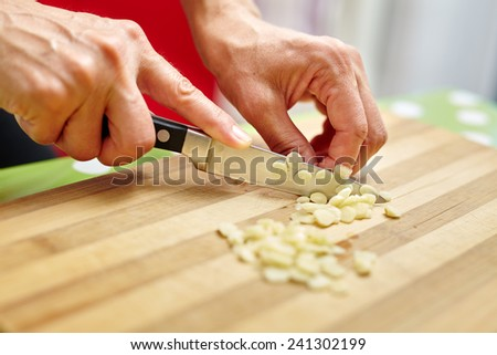 Woman hands chopping garlic on a wooden board
