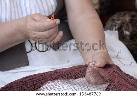 Woman hands creating a net. Needlework, traditional labor.