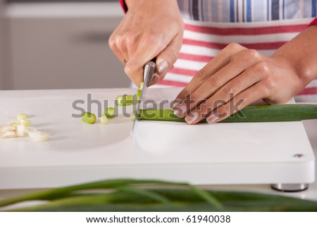 Woman hands cutting the spring onions with a big knife - stock photo
