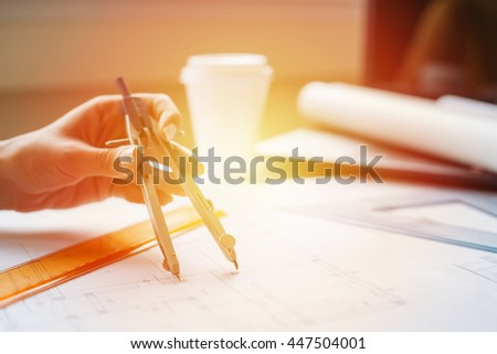 Woman hands drawing blueprints with a compass tool - stock photo