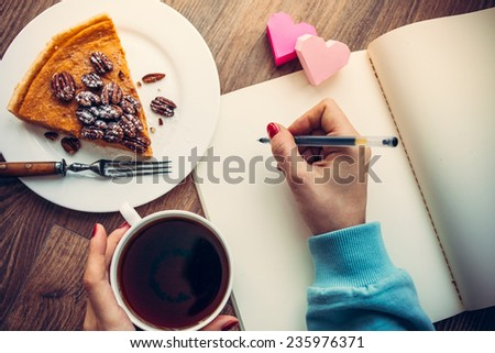 Woman hands drawing or writing, tea, pumpkin cake on wooden table. Toned picture - stock photo