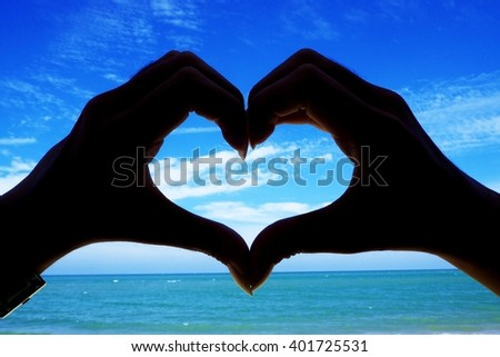 woman hands forming a heart over the blue sky - stock photo