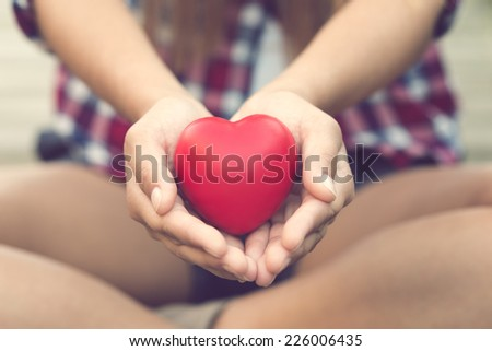 Woman hands giving a heart for you - stock photo