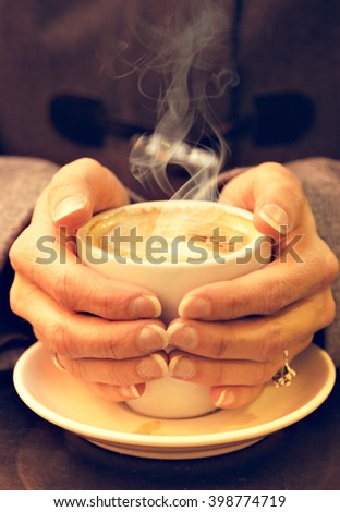 Woman hands hold a cup of coffee. Vertical image. Vintage style.