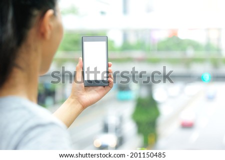 woman hands hold smart phone in modern city  - stock photo
