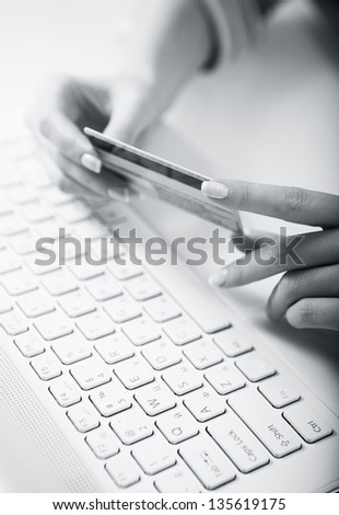 Woman' hands holding a credit card above a keybord getting ready to enter data - stock photo