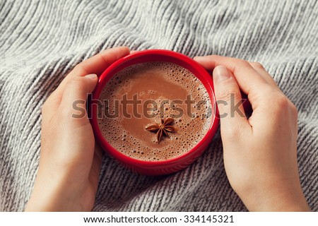 Woman hands holding a cup of hot cocoa or hot chocolate on knitted background, traditional beverage for winter time, lifestyle photo, top view - stock photo