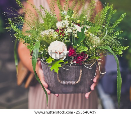 Woman hands holding a metal basket of flowers. Wedding bouquet looking like harvest. Vintage coloring - stock photo