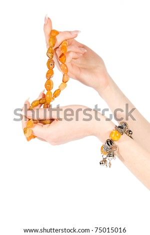 Woman hands holding amber necklace and bracelet on white - stock photo
