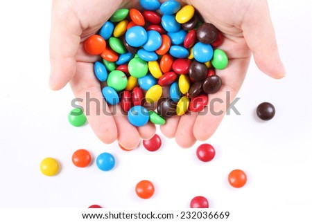 Woman hands holding colorful chocolate candies isolated on white - stock photo