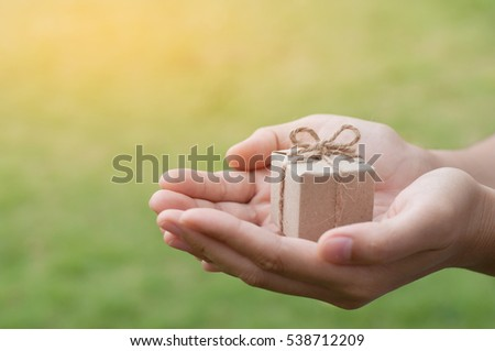 Woman hands holding gift box on natural background at outdoor park, Christmas and New Year concept. copy space.