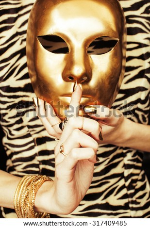 woman hands holding golden carnival mask, rich luxury manicure and jewelry close up on zebra print - stock photo