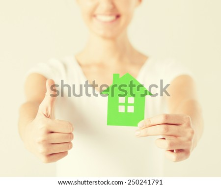 woman hands holding green house showing thumbs up - stock photo