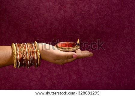 woman hands holding lantern (oil lamp) during diwali festival of lights