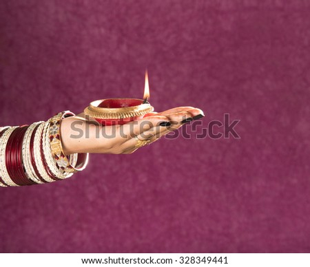 woman hands holding lantern (oil lamp) during diwali festival of lights on beautiful background