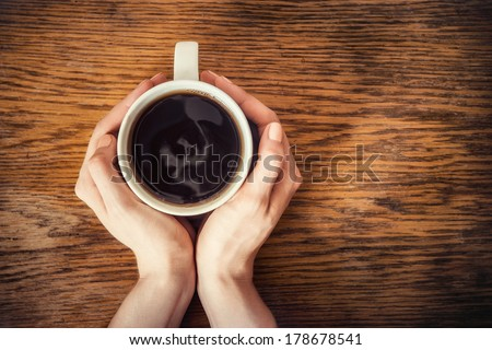 woman hands holding mug of hot drink that standing on wooden table - stock photo