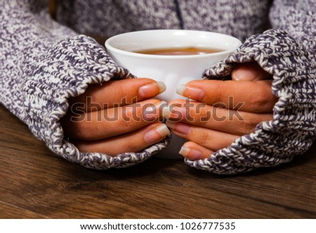 woman hands holding mug of hot tea drink on wooden table