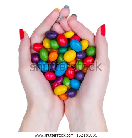 Woman hands holding multi-colored candy isolated on white background - stock photo