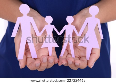 Woman hands holding paper family close up