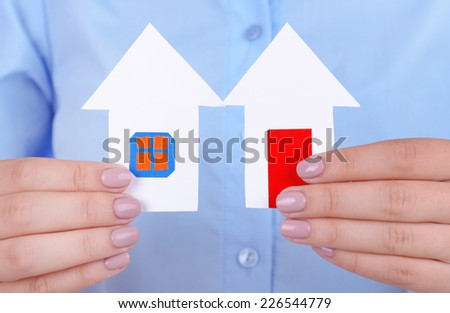 Woman hands holding paper houses close up