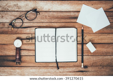 woman hands holding pencil and rubber eraser writing down on the book Top View with Copy Space, on vintage background. - stock photo