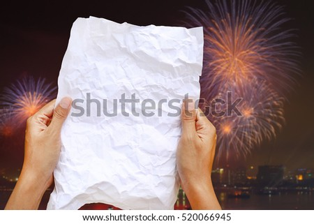 Woman hands holding square crumpled paper against Blur background of new year fireworks.