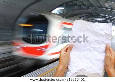 Woman hands holding square crumpled paper against speed train transport background.