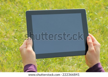 Woman hands holding tablet PC on green grass background - stock photo