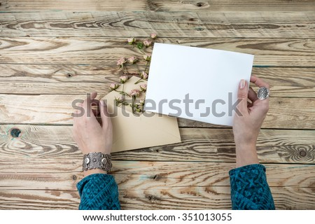 Woman hands holding the letter reading. Invitation (recognition, novelty, news, note). Retro style. The texture of natural wood countertop table. Top view