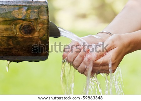 Woman hands holding water coming from a spring. - stock photo