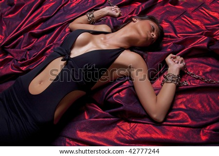 Woman Hands In Chains On Red Satin - stock photo