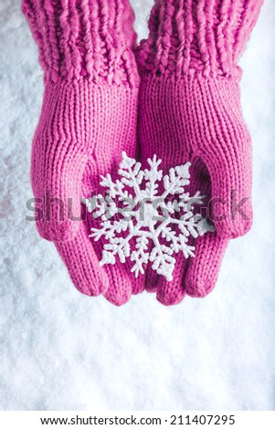 Woman hands in light pink knitted mittens with sparkling wonderful snowflake on a white snow background. Winter and Christmas concept. - stock photo