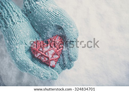 Woman hands in light teal knitted mittens are holding a beautiful glossy red heart in a snow winter background. Love and St. Valentine concept. - stock photo