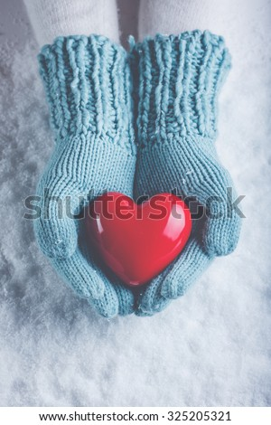 Woman hands in light teal knitted mittens are holding a beautiful glossy red heart in a snow winter background. Love and St. Valentine cozy concept.